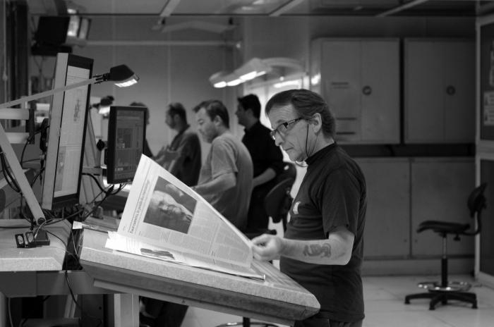 Des ouvriers contrôlent l'équilibre des couleurs lors de l'impression du journal.